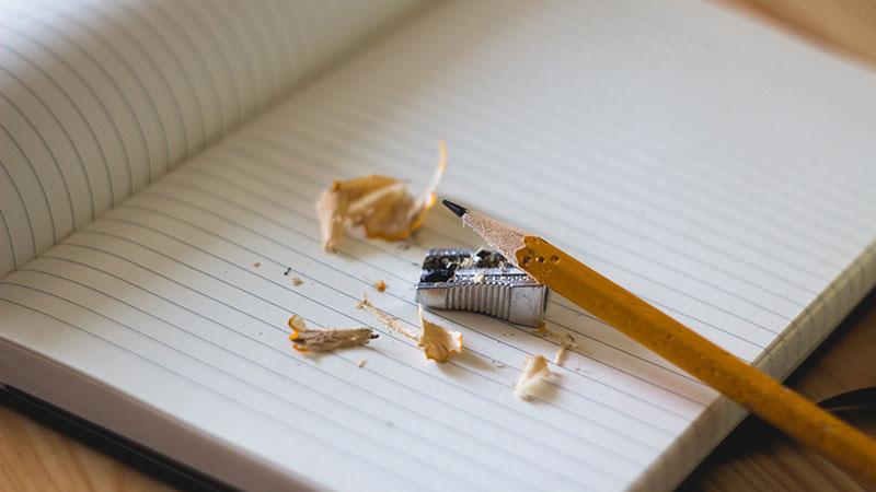 Soeben angespitzter Bleistift auf leeren Notizbuch