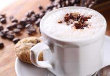 Eine Tasse Cappuccino, daneben liegen Kaffeebohnen.