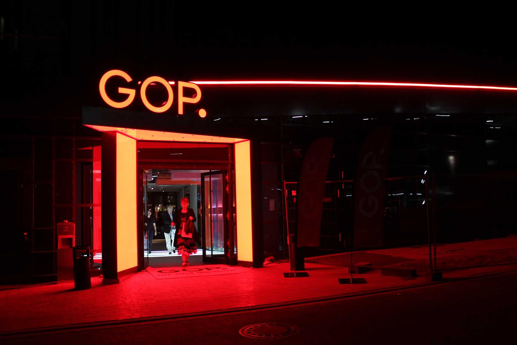 """Ein leuchtend rot umrandeter Eingang, darüber ebenso leuchtend der Schriftzug """"GOP.""""."""