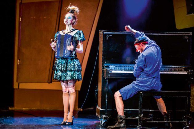 Eine Frau mit Akkordeon, daneben ein Mann mit Clownsschminke am Klavier.