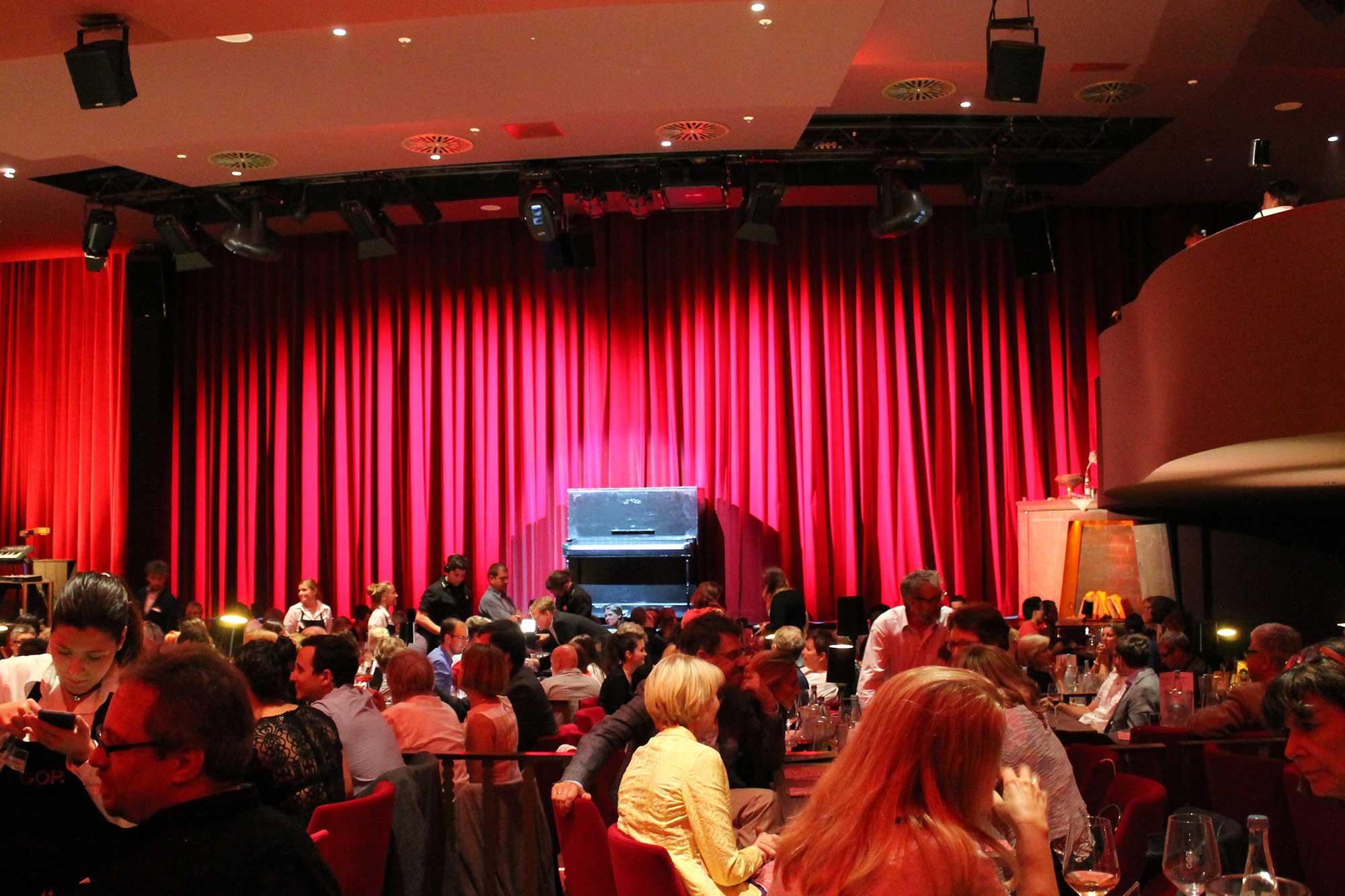 Ein roter Vorhang verhüllt die Bühne, davor steht ein schwarzes Piano. Im Vordergrund ganz viele Menschen an Tischen.