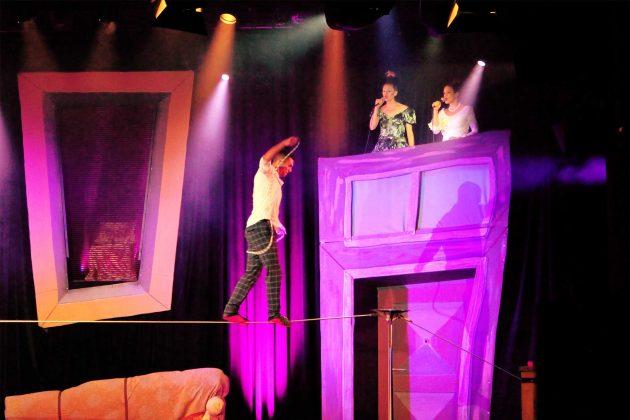 Ein Mann tanzt auf einem Seil. Erhoben rechts über ihm zwei Frauen, die in Mikrofone singen.