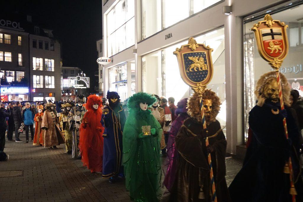 Carnevale die Venezia: hinter den Wappen der Städte Bonn und Venedig flanierten nach dem Vorbild der berühmten Karnevalskostüme Venedigs gekleidete Gestalten gemessenen Schrittes durch die City.