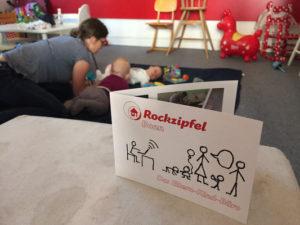 Ein aufgestellter Flyer, dahinter eine Mutter, die mit Kindern spielt