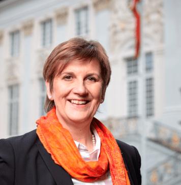 Claudia Lücking-Michel steht lächelnd vor dem Bonner Rathaus