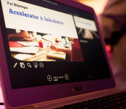 """Eine Folie der Präsentation ist auf dem Laptop sichtbar, auf ihr steht: """"Für Startups: Accelerator & Inkubator"""""""