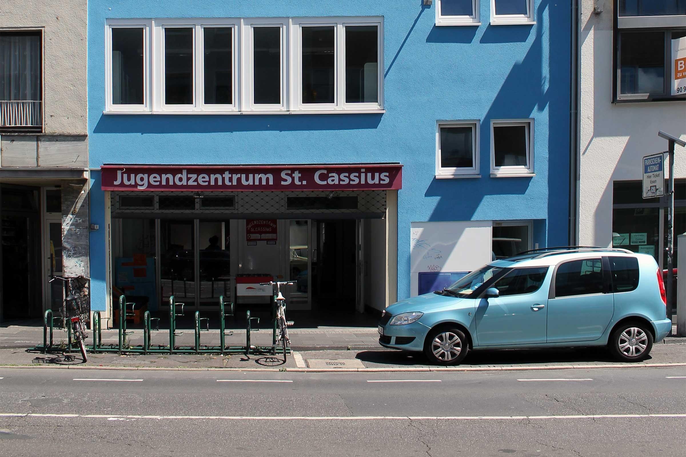 Ein hellblaues Gebäude, unten ein großer Eingang. Darüber in weißer Schrift auf rotem Grund: Jugendzentrum St. Cassius