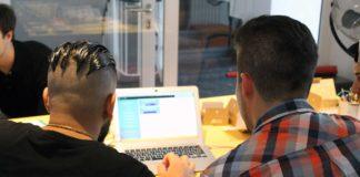 Ein Junge und ein Mann sitzen vor einem Laptop und betrachten den Bildschirm. Die Aufnahme zeigt die beiden nur von hinten.