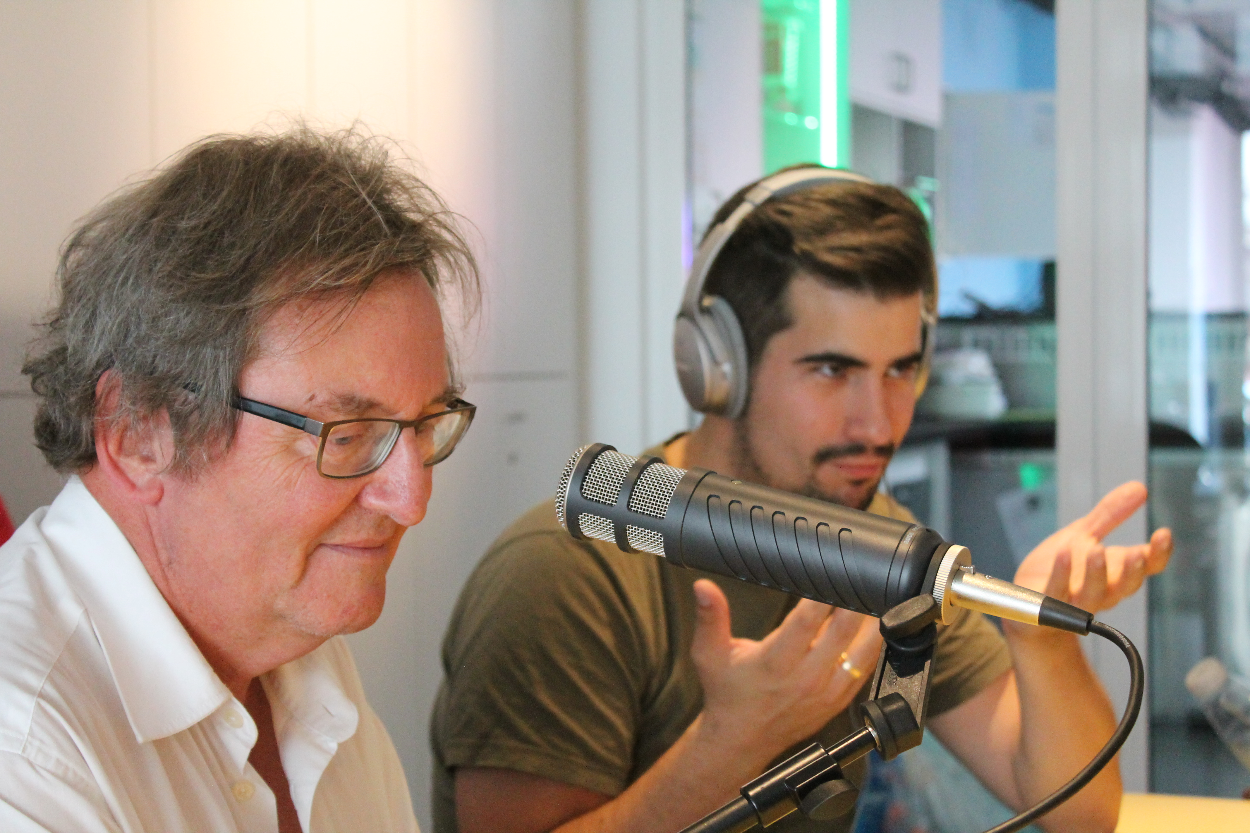 Ein älterer Mann im Vordergrund spricht in ein Mikrofon, dahinter ein jüngerer, der gestikuliert und Kopfhörer trägt.