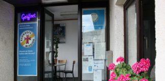 """Eine Glastür, links eine Leuchtreklame """"Geöffnet"""", darunter ein Schild """"Bahnhofsmission""""."""