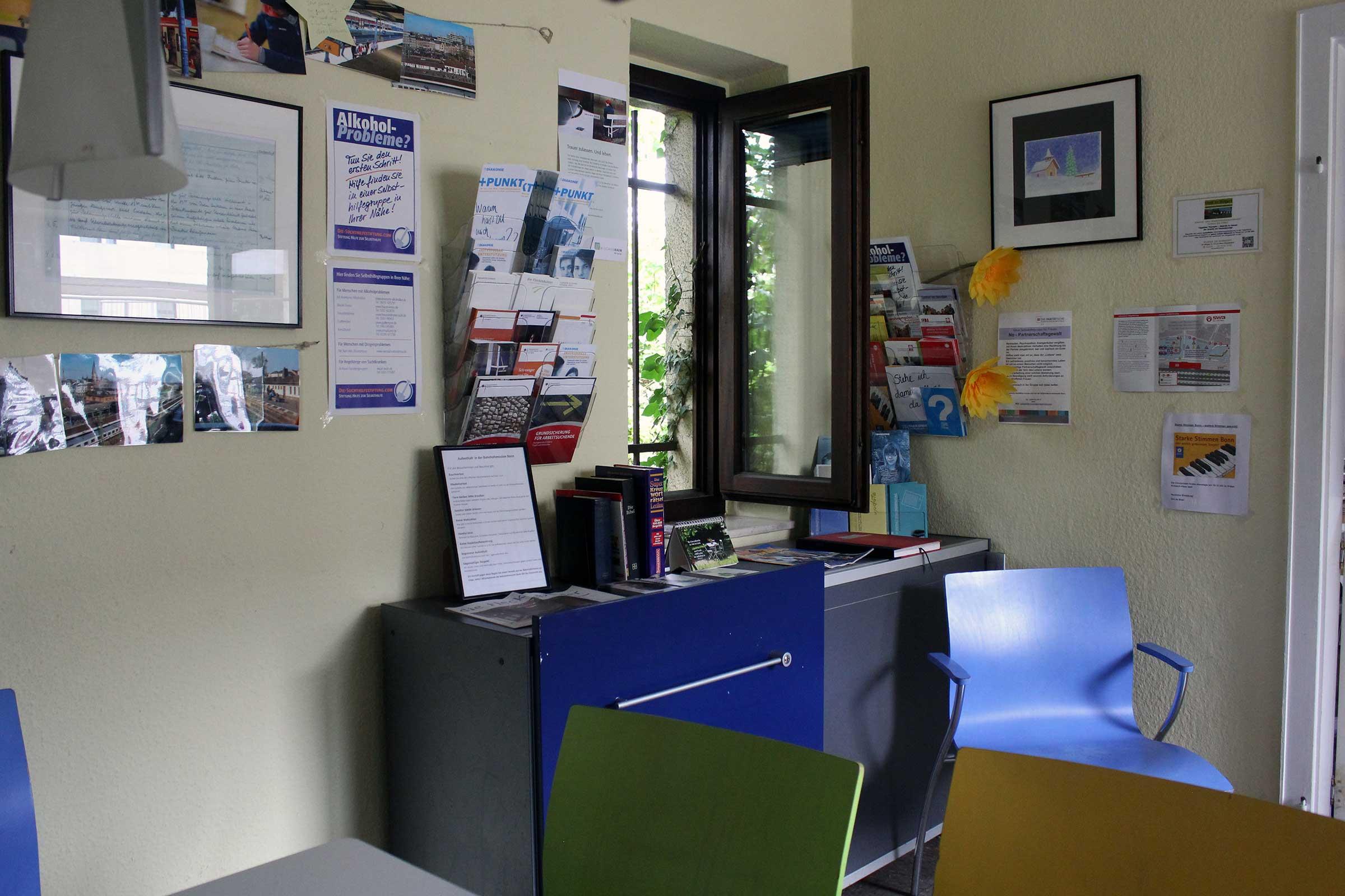 """Teil eines Tisches mit zwei Stühlen, dahinter an der Wand etliche Poster, auf denen zum Beispiel steht """"Alkoholprobleme?"""". Rechts ein geöffnetes Fenster mit Gitter davor."""