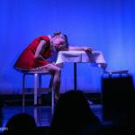 Eine Frau in einem kurzen roten Kleid sitzt an einem Tisch, den Kopf auf der Tischplatte und scheint zu träumen