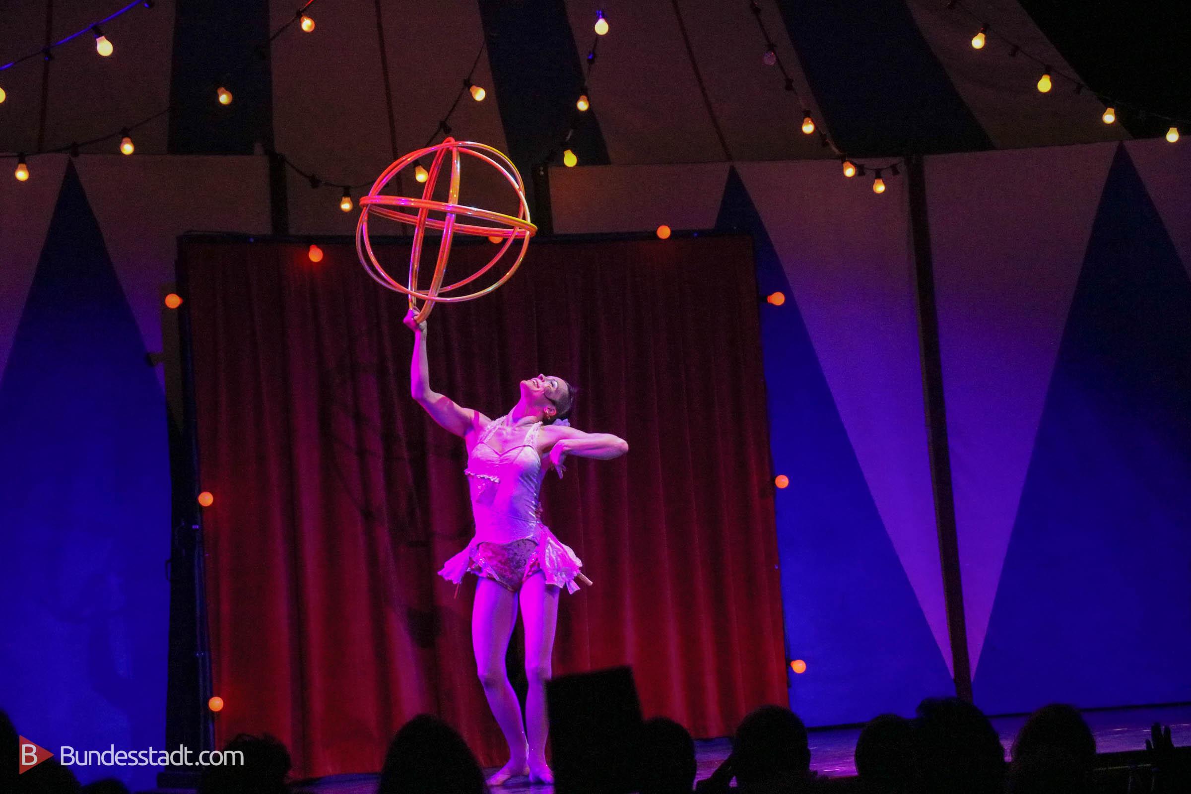 Mit Hula-Hoop-Reifen geformte Kugel steht die Artistin da wie der Preis Emmy