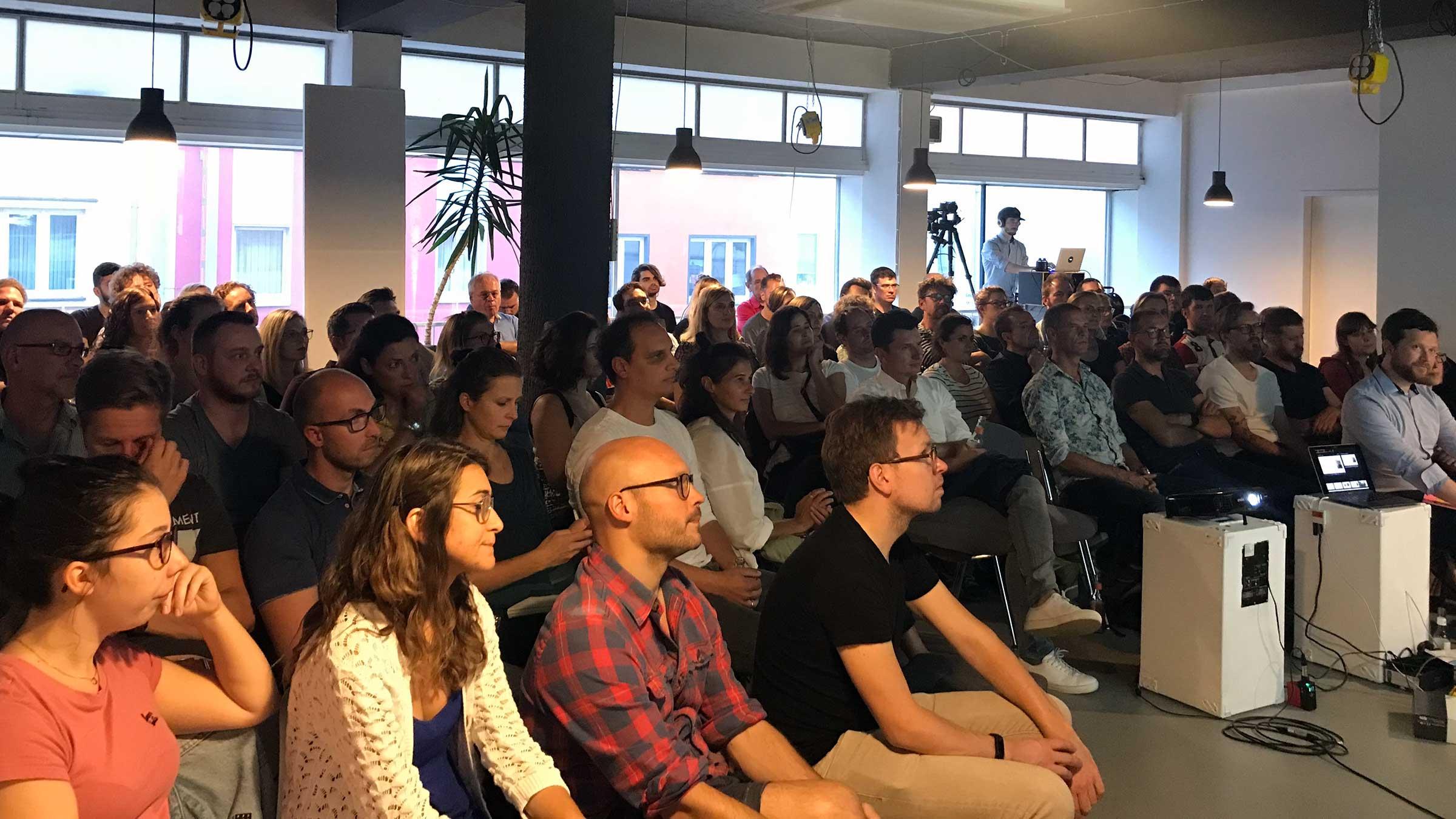 Ein Publikum von links vorne fotografiert. Alle blicken zur Bühne.