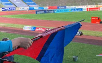 Ein Kind hält eine blau-rote Fahne, im Hintergrund das Stadion.