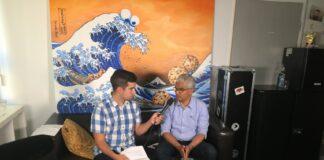 Zwei Männer sitzen auf einem Sofa unter einem Bild, das eine große Welle mit Cookie-Monster-Gesicht zeigt. Der linke Mann (Sascha) hält dem rechten (Sridharan) ein Mikrofon vor das Gesicht.