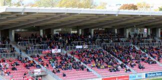 Eine überdachte Tribüne mit mehren Hundert Menschen auf roten Sitzen. Es gibt einige Lücken, die vorderen Reihen sind fast gar nicht gefüllt.