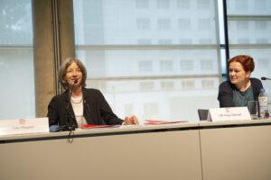 Zwei Frauen sitzen an einem Tisch, vor sich Mikrofone. Dörner sieht Wagner lächelnd an, die lächelt ins Publikum.