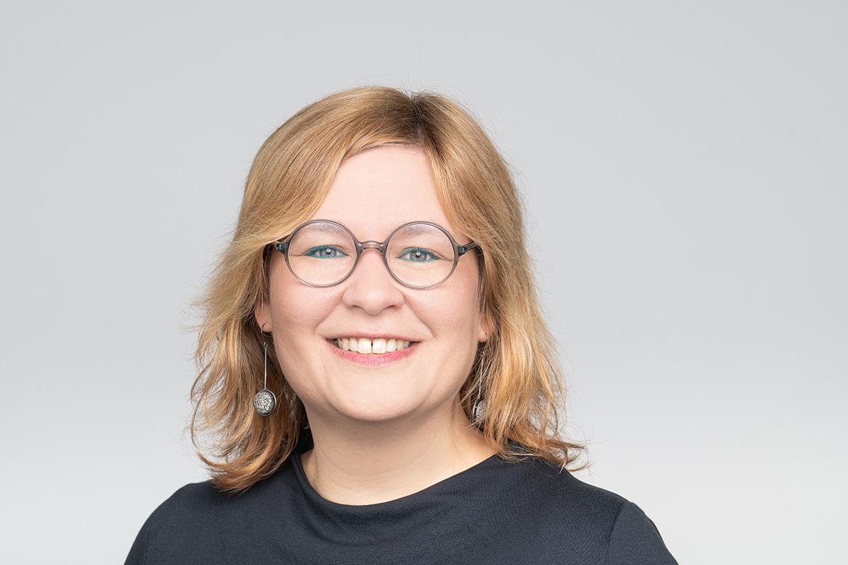 Eine blonde Frau mit runder Brille, sie lächelt.